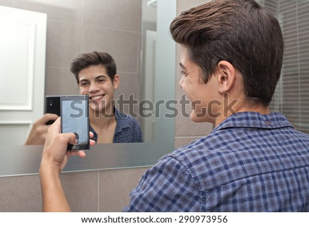 Portrait of a smiling young adolescent teenager man using a smartphone device to take selfies pictures of himself in a home bathroom mirror, networking in social media. Technology lifestyle at home.