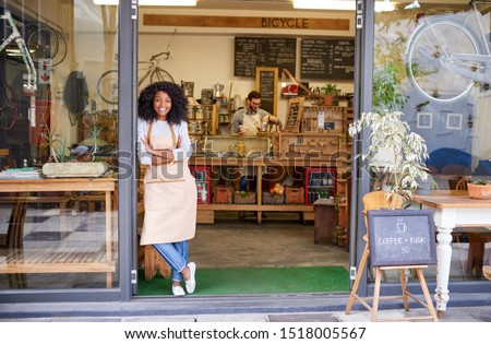 Portrait of a smiling young African American barista leaning with her arms crossed against the entrance of a trendy cafe