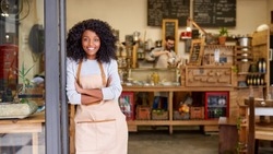 Portrait of a smiling young African American barista leaning with her arms crossed on the door of a trendy cafe
