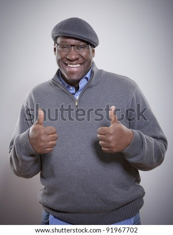 Portrait of a smiling young African American man giving thumbs up
