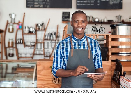 Portrait of a smiling young African entrepreneur in an apron leaning against the counter of his trendy cafe using a digital tablet #707830072