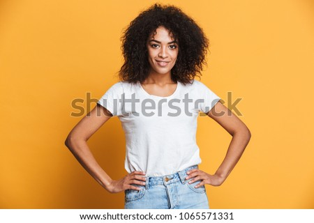 Portrait of a smiling young african woman holding hands on hips isolated over yellow background