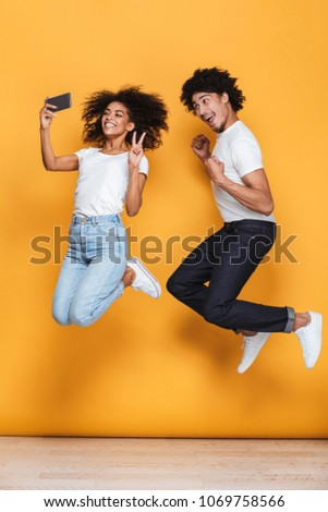 Portrait of a smiling young afro american couple taking a selfie while jumping isolated over yellow background