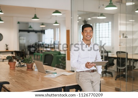Portrait of a smiling young Asian businessman leaning on his desk in a large modern office working online with a digital tablet