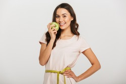 Portrait of a smiling young asian woman holding measuring tape around her waist and eating green apple over white background