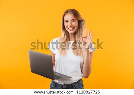 Portrait of a smiling young blonde girl holding laptop computer and showing ok gesture isolated over yellow background #1120827725