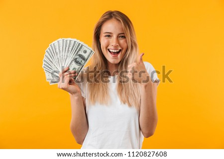 Portrait of a smiling young blonde girl showing bunch of money banknotes and giving thumbs up isolated over yellow background