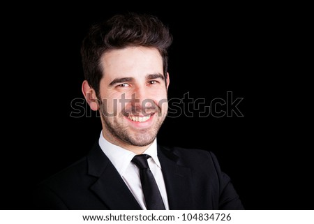 Portrait of a smiling young business man isolated on black background. - stock photo