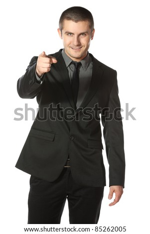 Portrait of a smiling young business man pointing at you over white background