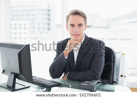 Portrait of a smiling young businessman in front of computer at office desk