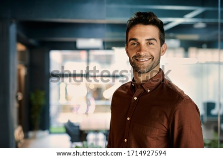 Portrait of a smiling young businessman standing alone in a dark office while working late