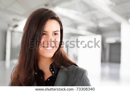 Portrait of a smiling young businesswoman. Blurred background.