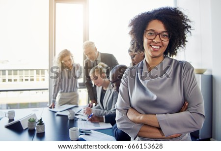 Portrait of a smiling young businesswoman standing with her arms crossed in a modern office with a group of colleagues working in the background
