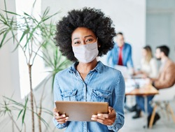 portrait of a smiling young businesswoman wearing a mask and holding a tablet in the office