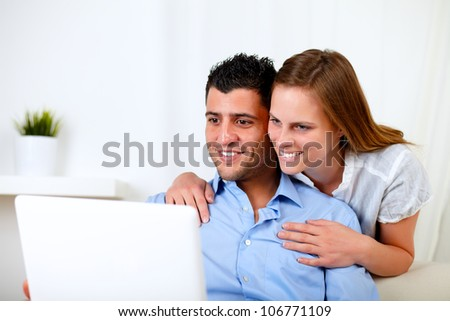 Portrait of a smiling young couple using laptop at home indoor - stock photo