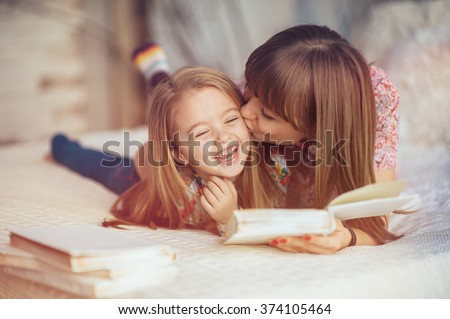 Portrait of a smiling young cute mother and daughter reading a book lying and relax in the bed in a bright big white room  #374105464