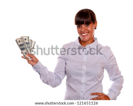 Portrait of a smiling young female holding cash money standing over white background