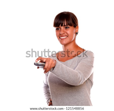 Portrait of a smiling young female using a tv remote against white background