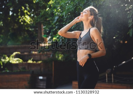 Portrait of a smiling young fitness girl listening to music through wireless earphones outdoors