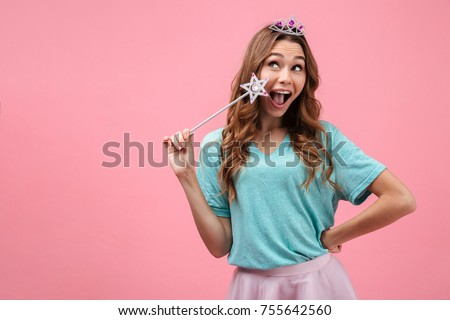 Portrait of a smiling young girl dressed in fairy costume holding magic wand while standing and looking away at copy space isolated over pink background #755642560