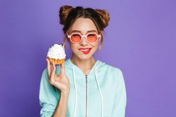 Portrait of a smiling young girl with bright makeup over violet background, holding cupcake
