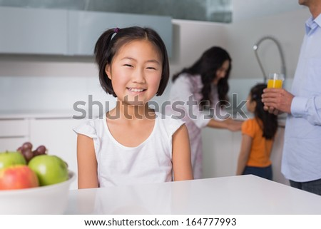 Portrait of a smiling young girl with family in the background at kitchen in home