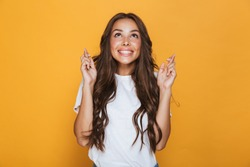 Portrait of a smiling young girl with long brunette hair standing over yellow background, holding fingers crossed for good luck