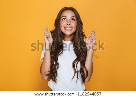 Portrait of a smiling young girl with long brunette hair standing over yellow background, holding fingers crossed for good luck #1182544057