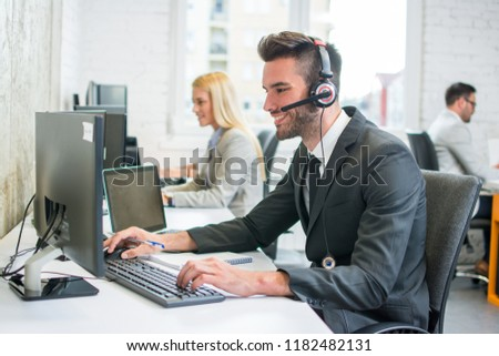 Portrait of a smiling young handsome man in formalwear with headset using computer in a office #1182482131