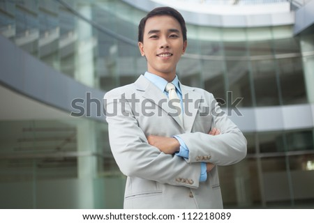 Portrait of a smiling young man appearing to be the owner of business