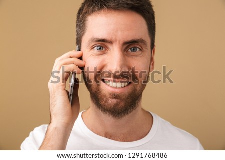 Portrait of a smiling young man casually dressed standing isolated over beige background, talking on mobile phone