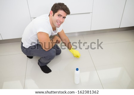 Portrait of a smiling young man cleaning the kitchen floor at house
