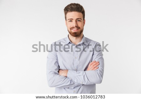 Portrait of a smiling young man dressed in shirt standing with arms folded isolated over white background