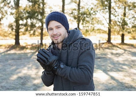 Portrait of a smiling young man in warm clothing shivering while having a walk in forest on a winter day