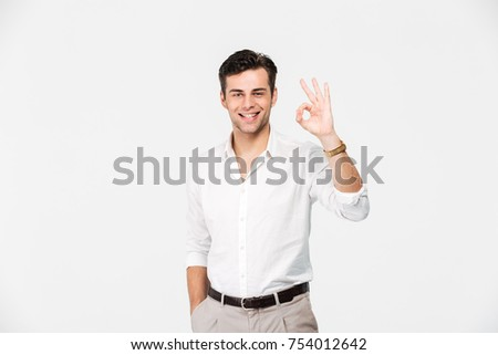 Portrait of a smiling young man in white shirt showing ok gesture while standing and looking at camera isolated over white background