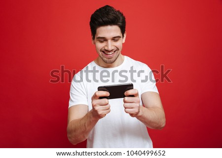 Portrait of a smiling young man in white t-shirt playing games on mobile phone isolated over red background