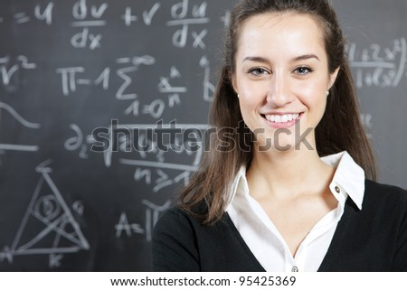 Portrait of a smiling young woman, college student or teacher in front of a blackboard