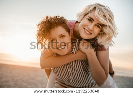 Portrait of a smiling young woman giving her girlfriend a piggyback while having fun together at a beach at sunset