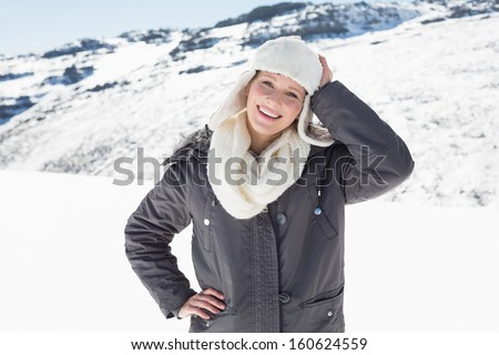 Portrait of a smiling young woman in warm clothing standing on snow covered landscape