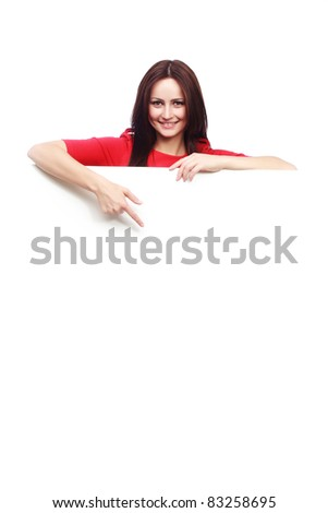 Portrait of a smiling young woman pointing at a blank board isolated on white