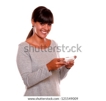 Portrait of a smiling young woman sending message by cellphone looking at you on isolated background