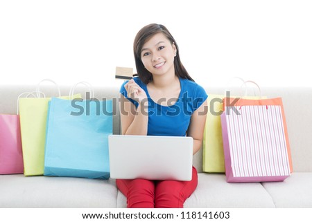 Portrait of a smiling young woman sitting among shopping-bags and purchasing online