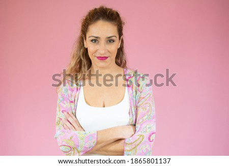 Portrait of a smiling young woman standing with arms folded isolated over pink background Stockfoto ©