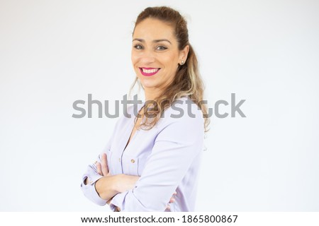 Portrait of a smiling young woman standing with arms folded isolated over white background Stockfoto ©