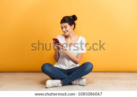 Portrait of a smiling young woman using mobile phone while sitting with legs crossed on a floor over yellow background #1085086067