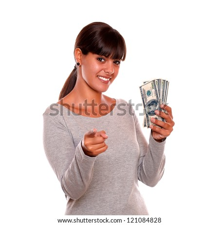 Portrait of a smiling young woman with money looking and pointing at you standing over white background