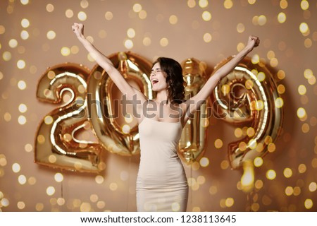 Portrait of a smiling youngPortrait of a joyful young beautiful woman spread her arms to the side and shouts hurray Under boke Having Fun With Gold 2019 Balloons