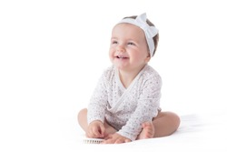 Portrait of a smilling baby girl with hair brush isolated on a white background