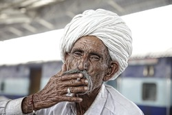 Portrait of a smoking Rajasthani Indian man with turban and a typical Rajasthani style beard.