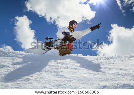 Portrait of a snowboarder in the winter resort, pointing the way to the mountains in the background of mountains and blue sky with clouds #168608306